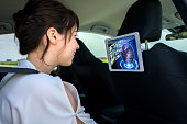 young woman watching a video at the rear seat of vehicle. automotive infotainment concept.