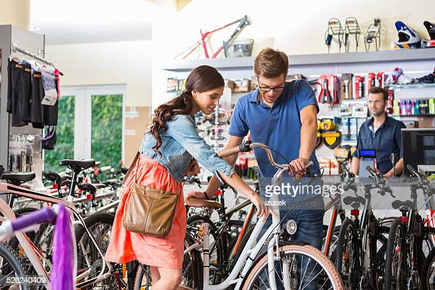 Young woman watching bicycle in sport store