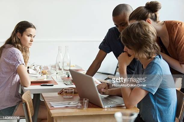 Young woman watching friends using laptop computer