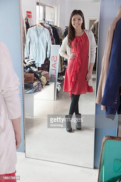 Young woman watching herself at the mirror at fashion store