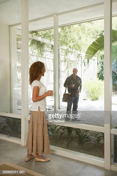 Young woman watching man through glass windows