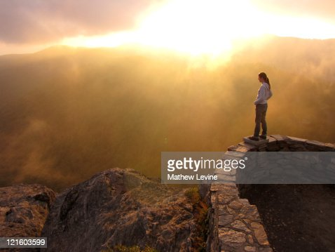 Young woman watching sunset from rocky mountaintop