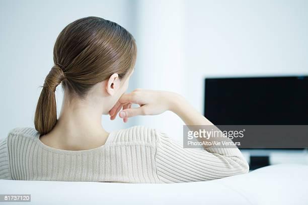Young woman watching TV, rear view