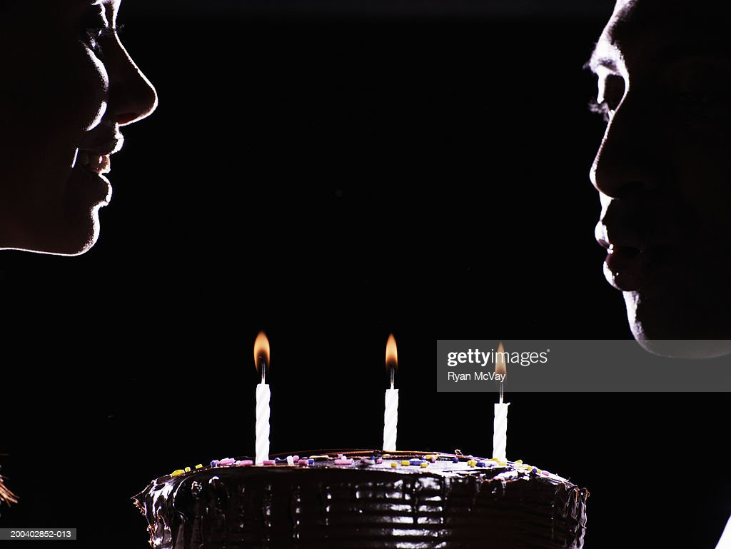 Young woman watching young man blow out candles on cake, side view : Stock Photo