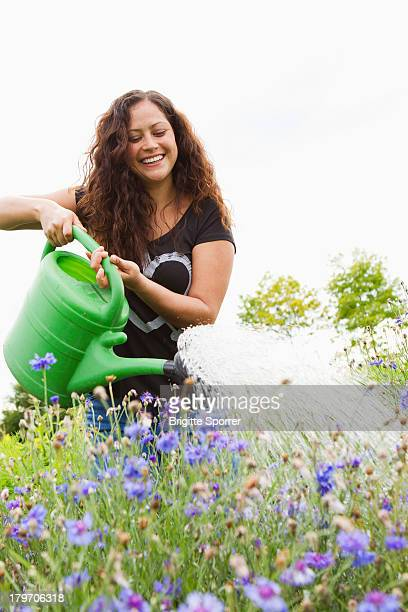Young woman watering flowers in allotment
