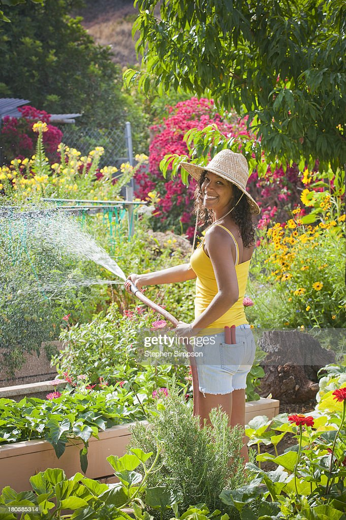 young woman watering large vegetable garden : Stock Photo