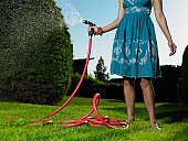 Young woman watering lawn, low section