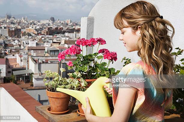 Young woman watering potted plants