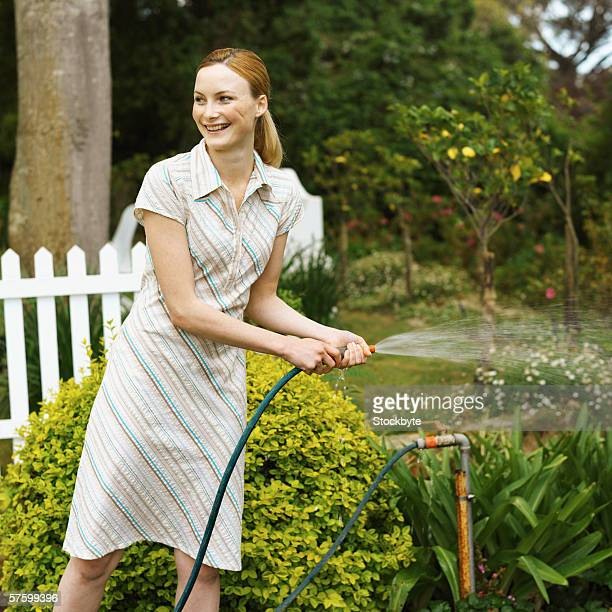 Young woman watering the garden with a hose