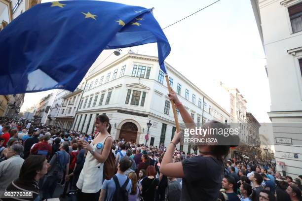 A young woman waves the European flag as she demonstrates in front of the Central European University in Budapest on April 2 following allegations of...