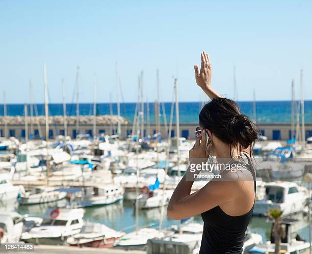 Young Woman Waving and Talking on Mobile Phone