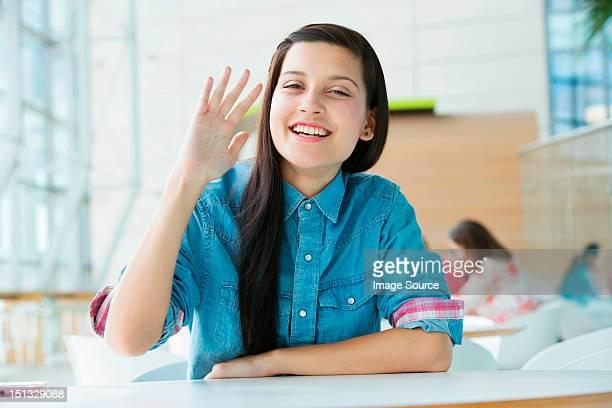 Young woman waving at camera