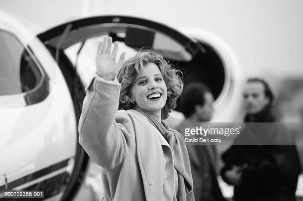 Young woman waving hand and smiling (B&W)