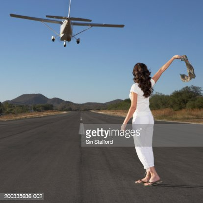 Young woman waving scarf to private plane in flight