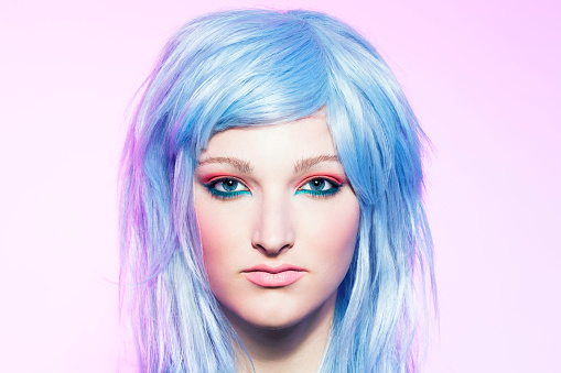 Young woman wearing a blue hair wig, portrait.