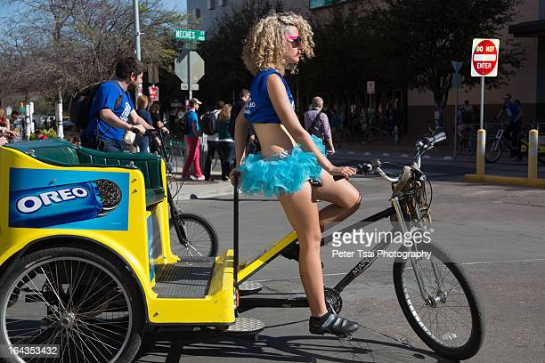 CONTENT] A young woman wearing a bright blue tutu drives an OREO branded pedicab in Austin Texas during the SXSW 2013 Conference