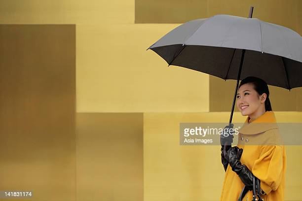 Young woman wearing a coat and gloves holding an umbrella