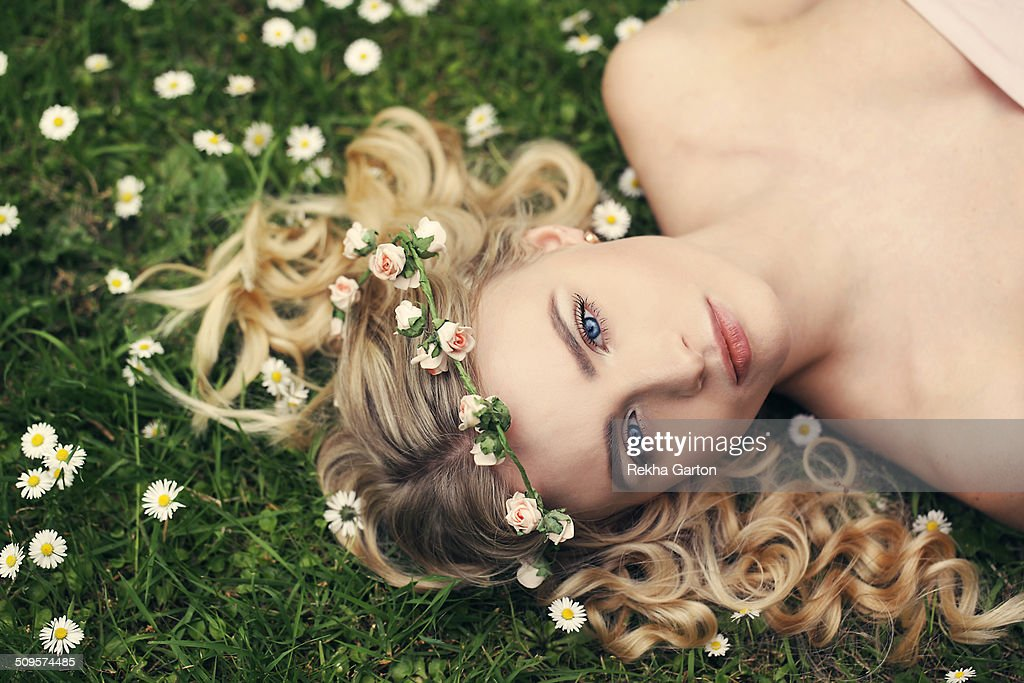 Young woman wearing a flower crown in a flowers