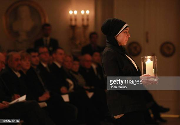 A young woman wearing a headscarf carries a candle to the stage at a state commemoration for the victims of the NSU neoNazi murders at the...