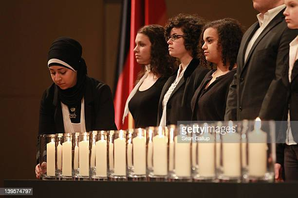 A young woman wearing a headscarf places a candle among others at a state commemoration for the victims of the NSU neoNazi murders at the Konzerthaus...