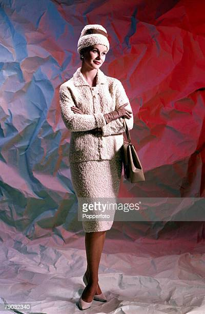 Young woman wearing a knitted boucle two piece suit in soft white with matching hat 1961
