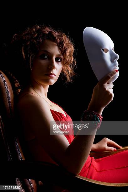 Young woman wearing a red dress holding white mask