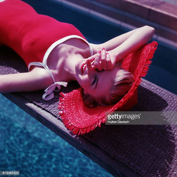 A young woman wearing a red swimsuit and sunhat shades her eyes from the sun as she relaxes above the crystalline waters of a swimming pool Ca 1955