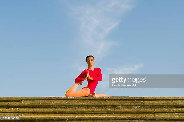Young woman wearing a redorange body suit is practising HathaYoga outdoor showing the pose kapotasana dove pose / pigeon pose