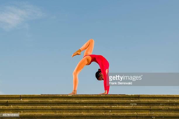 Young woman wearing a redorange body suit is practising HathaYoga outdoor showing the pose chakrasana / urdhva dhanurasana wheel pose