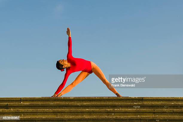 Young woman wearing a redorange body suit is practising HathaYoga outdoor showing the pose trikonasana triangle