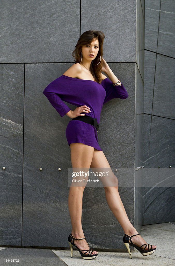 Young Woman Wearing A Short Purple Dress And High Heels Leaning ...