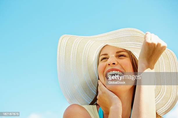 Young woman wearing a sun hat and laughing