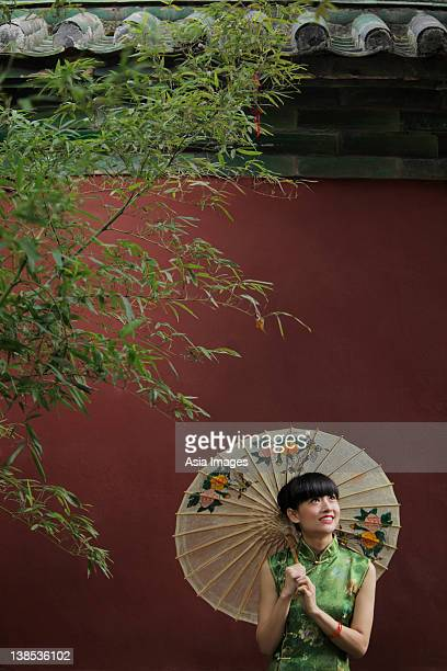 Young woman wearing a traditional Chinese dress holding an umbrella