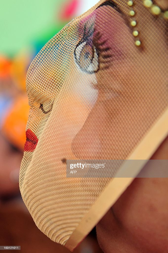 A young woman wearing a traditional mask takes part in a procession during celebrations for San Jeronimo, the patron saint of Masaya, 30 km from Managua, on September 30, 2012. During the procession the image of San Jeronimo is taken from the San Jeronimo church to Nuestra Señora de la Asuncion church and back. AFP PHOTO/Hector RETAMAL