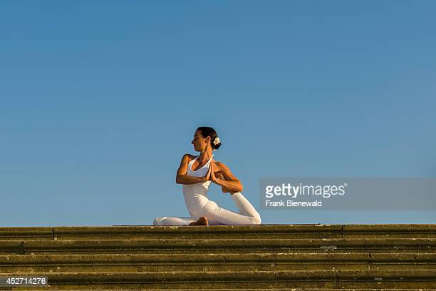 Young woman wearing a white body suit is practising HathaYoga outdoor showing the pose kapotasana dove pose / pigeon pose