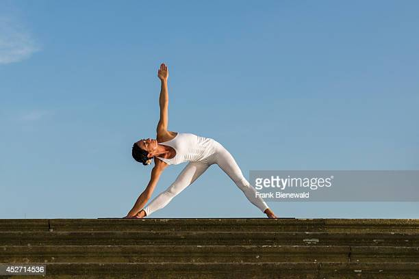 Young woman wearing a white body suit is practising HathaYoga outdoor showing the pose trikonasana triangle