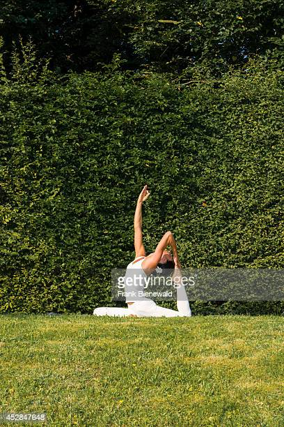 Young woman wearing a white body suit is practising HathaYoga outdoor between trees showing the pose kapotasana dove pose / pigeon pose