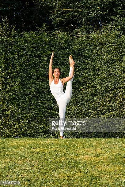 Young woman wearing a white body suit is practising HathaYoga outdoor between trees showing the pose anjaneyasana raised hand to foot pose