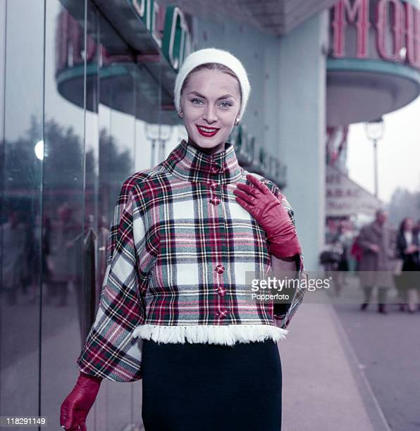 A young woman wearing a white knit cap and a tartan jacket with red gloves on a Paris street circa 1960