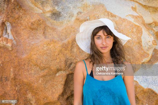 Young woman wearing a white sun hat enjoying peaceful seaside vacation, standing in on the beach by the rock cliffside.