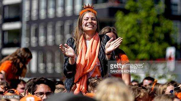 A young woman wearing an orange crown and scarf sits on a person's shoulders during a party of the Dutch radio station Radio 538 in Breda the...
