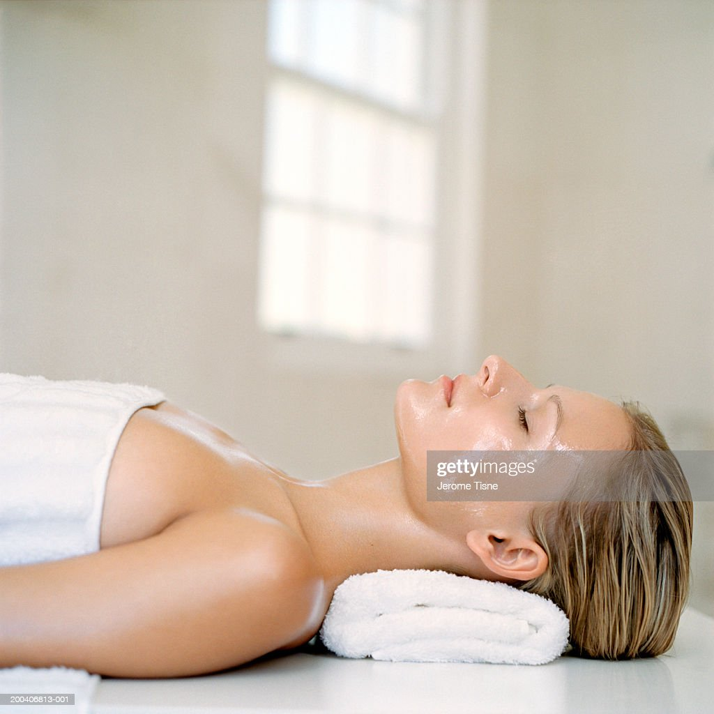 Young woman wearing beauty treatment on face and body, side view : Stock Photo