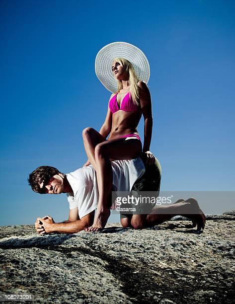 Young Woman Wearing Bikini and Sitting on Man's Back