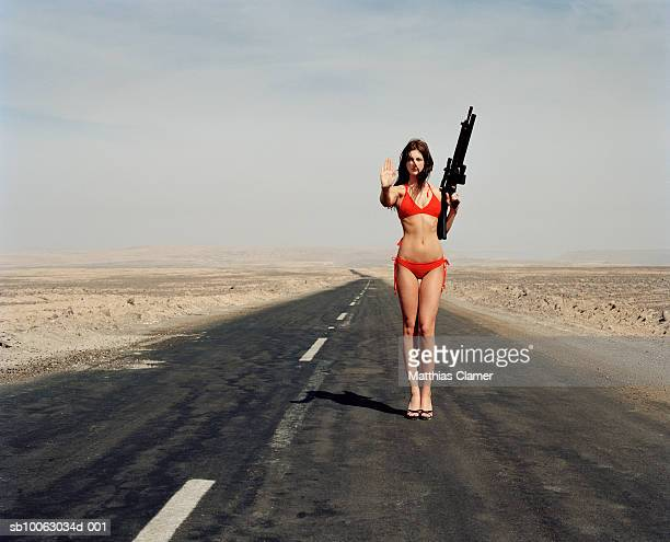 Young woman wearing bikini holding machinegun making a stop sign with hand