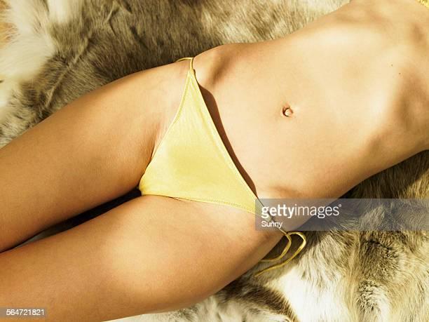 Young Woman Wearing Bikini Lying on Fur