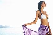 Young woman wearing bikini top and sarong, standing on beach