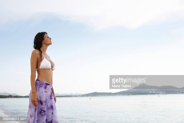 Young woman wearing bikini top and sarong, standing on beach