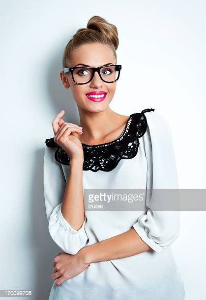Young woman wearing bit glasses, arms folded