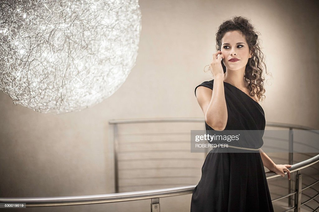 Young woman wearing black dress on cell phone, portrait