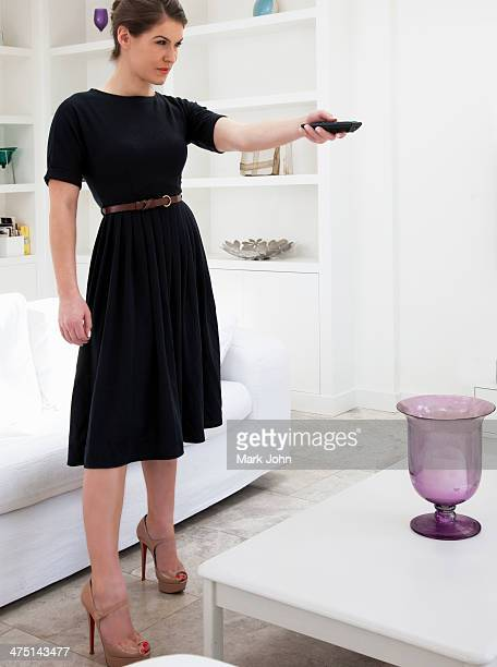 Young woman wearing black dress using remote control